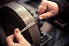 Sharpening scissors detail. Close up shot of a man`s hands sharpening a scissors stock photography