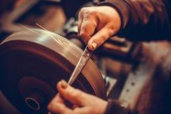 Sharpening scissors detail. Close up shot of a man`s hands sharpening a scissors stock images