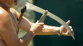 Sharpening scythe in hot summer day Royalty Free Stock Photography