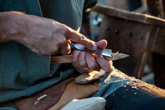 Sharpening a wood stick with a blade Royalty Free Stock Image