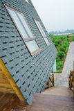 Sharply pitched roof of wooden house in orchard Royalty Free Stock Photos