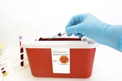 Sharps Container. Technician drops syringe into sharps container royalty free stock photos