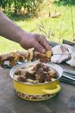 shashlik为烤肉格栅做准备 人手在串上把用卤汁泡的肉放片断  在串的烤肉串 自由空间为 免版税库存图片