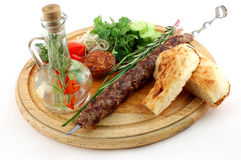 Shashlik. Barbecue with tomatoes with seasoning and greens on a wooden support on a white background Stock Photos