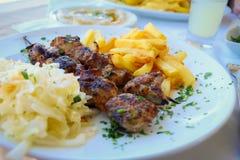 Shashlik arrostito con le patate fritte sul piatto Immagini Stock