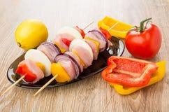 Shashlik crudo del pollo en los pinchos en el plato marrón, pimienta, tomates Imagen de archivo