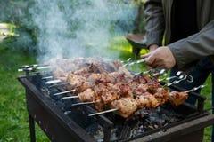 Shashlik eller shashlyk som förbereder sig på ett grillfestgaller över kol Grillade kuber av grisköttkött på metallsteknålen utom royaltyfri bild