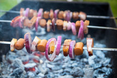 Shashlik with frankfurter, bacon and onion. Laying on the grill Royalty Free Stock Images
