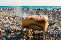 Mangal with shashlik on pebble beach Stock Photo