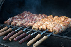 Shashlik kebab cooking on skewer. At grill barbecue Royalty Free Stock Photo