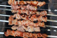Shashlik meat on brazier mangal roasting  in row Stock Image