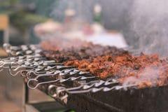 Shashlik o shashlyk che prepara su una griglia del barbecue sopra carbone Cubi arrostiti della carne suina sullo spiedo del metal immagini stock