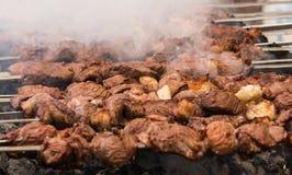 Shashlik oder shashlyk, die auf einen Grillgrill ?ber Holzkohle sich vorbereiten Gegrillte W?rfel des Schweinefleischs auf Metall stockfotografie