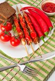 Shashlik on a plate with cherry and chili. Stock Photo
