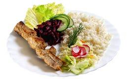 Shashlik with rice. And some salads on white dish. Isolated on white background Royalty Free Stock Photos