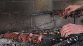 Shashlik sur des brochettes a fait cuire sur le barbecue au-dessus des charbons dans le restaurant Le bel intérieur du restaurant clips vidéos