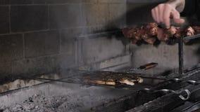 Shashlik sur des brochettes a fait cuire sur le barbecue au-dessus des charbons dans le restaurant Le bel intérieur du restaurant banque de vidéos