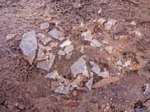 Shattered broken ice on mud floor walk surface outside texture w stock photography