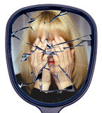 Shattered and Broken Life. A woman covers her face reflected in a  broken mirror or the shattered life concept Stock Photo