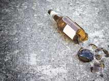 Shattered brown beer bottle resting on the ground Royalty Free Stock Photos