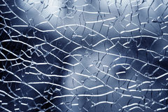 Shattered glass. Close up of shattered glass on blue background Stock Images