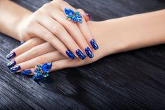 Shattered glass blue manicure on black background. Shattered glass blue manicure on black wooden background stock photography