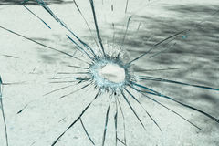 A shattered glass with a hole in the middle. Stock Photos