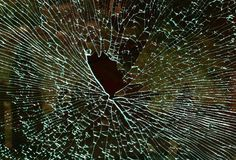 Shattered glass window displaying interesting patterns. A shattered glass safety window displaying a large hole from impact and interesting patterns Royalty Free Stock Image