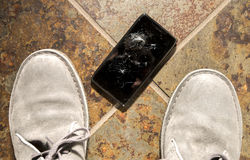 Shattered Smartphone. A smartphone lies broken between the shoes of its owner just after being dropped Stock Photo