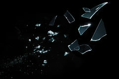 Shattered and splitted glass Pieces isolated on black. Sharp pieces of glass flying to right side Stock Photo