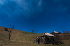 Shattered Wooden Cottage under Stars. Shattered wooden cottage on top of the hill under the blue sky with lots of stars. Night landscape in Carpathians, Romania Royalty Free Stock Photos