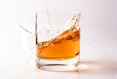 A shattering glass of brandy or brandy. Shards of glass and splashes of drink.  royalty free stock photography