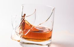 A shattering glass of brandy or brandy. Shards of glass and splashes of drink.  royalty free stock image