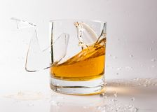 A shattering glass of brandy or brandy. Shards of glass and splashes of drink.  stock image