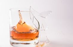 A shattering glass of brandy or brandy. Shards of glass and splashes of drink.  royalty free stock photo