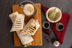 Shaurma chicken roll in a pita with fresh vegetables and cream sauce composition on wooden background Stock Image