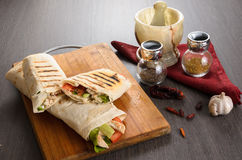 Shaurma chicken roll in a pita with fresh vegetables and cream sauce composition on wooden background Stock Photos