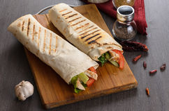 Shaurma chicken roll in a pita with fresh vegetables and cream sauce composition on wooden background Royalty Free Stock Images