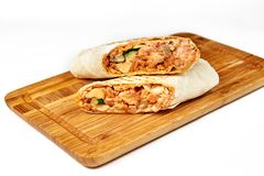 Shaurma or giros pita, roll in pita bread with meat and vegetables stock photo