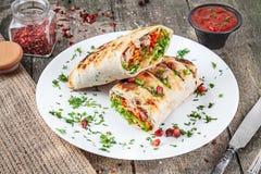 Shaurma shawermaen, kebab tjänade som på den vita plattan med sås Strikt vegetarianmat med falafelen Arabisk eller östlig kokkons arkivbild