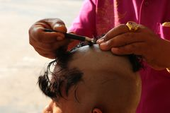 Shave hands ordained hair. Close-up photos of light, hands of men being shaved on the head of those who are ordained in Buddhism stock photo