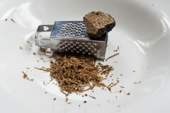 Black truffles on white plate with mini grater. Shaved black transyilvanian truffle on white plate Stock Photos
