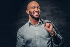 Shaved head male with tattooed arm holds jacket on his shoulder. Portrait of a shaved head male with tattooed arm holds jacket on his shoulder Royalty Free Stock Photography
