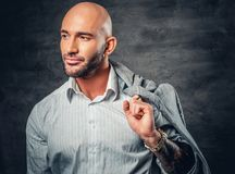 Shaved head male with tattooed arm holds jacket on his shoulder. Portrait of a shaved head male with tattooed arm holds jacket on his shoulder Royalty Free Stock Photo
