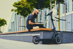 Bearded male using a laptop after electric scooter ride. Shaved head tattooed, bearded male using a laptop over modern building background after the electric Royalty Free Stock Image