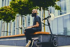 Bearded male using a laptop after electric scooter ride. Shaved head tattooed, bearded male using a laptop over modern building background after the electric Stock Image