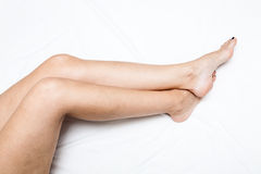 Shaved and smooth woman's long legs.  on white. Royalty Free Stock Photography