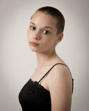 Shaven Bald Teenage Girl With Black Top and Bare Shoulders Royalty Free Stock Image