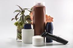 Shaver, soap, shampoo, deodorant, cream set. Flowers and isolated background royalty free stock photo