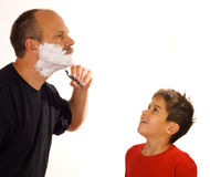 Shaving. Little boy looking at his father shaving stock photos